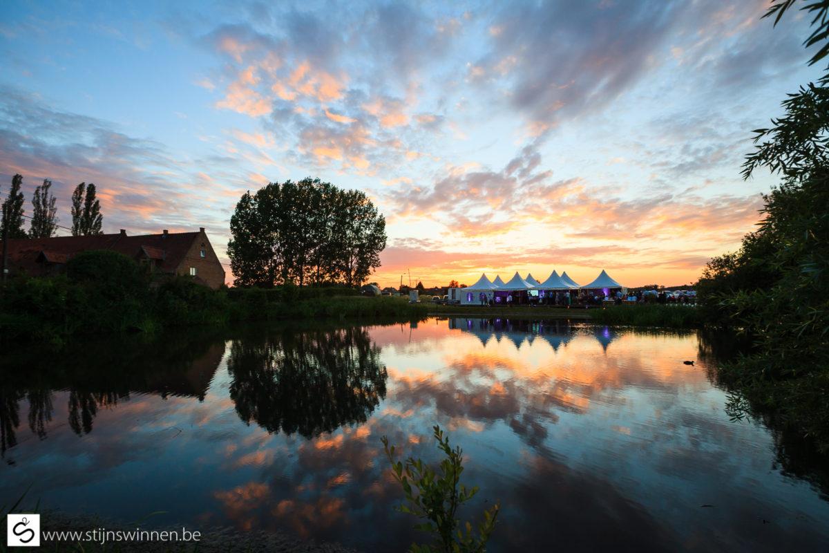 Reflecties van de feesttent in het water bij ondergaande zon
